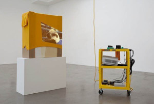 Rachel Harrison, AA, 2010. Wood, bubble wrap, cardboard, acrylic, tennis shirt, A/V cart, DVD player, speakers, projector, extension cord, five hair rollers, pack of gum, ear plugs, and American Apparel video, color, sound, 18 minutes (2009). Courtesy of the artist, Greene Naftali, New York and Regen Projects, Los Angeles. Photography by Brian Forrest.